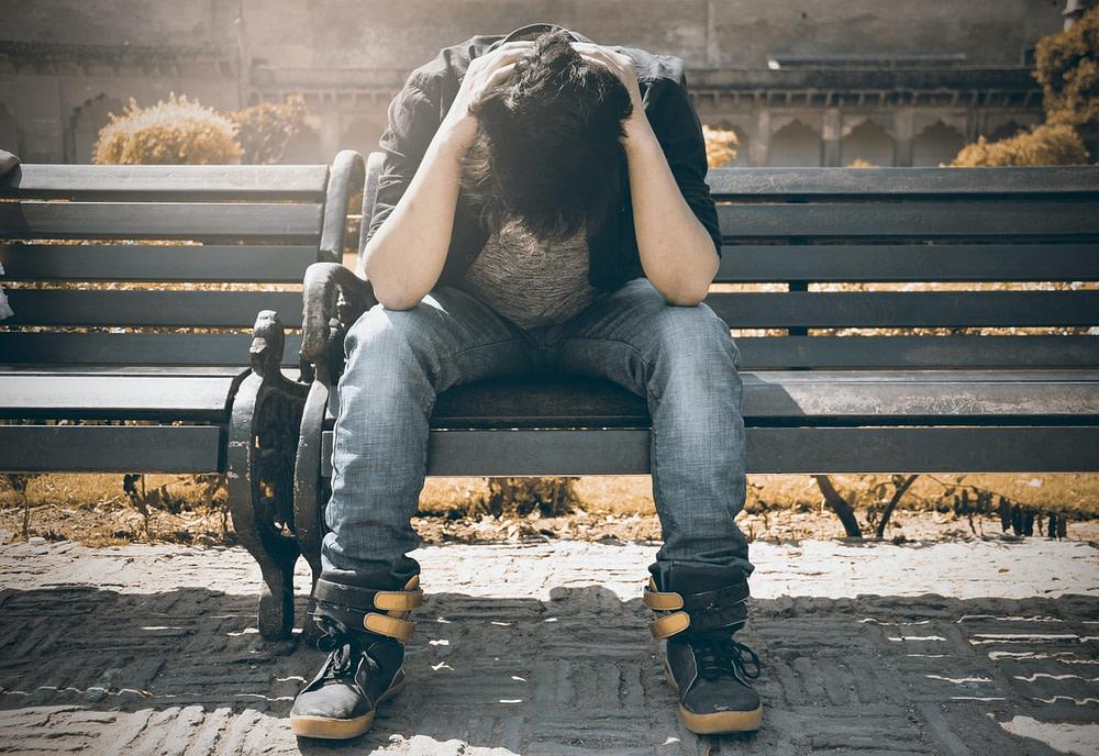Jugendlicher auf einer Bank, niedergeschlagen